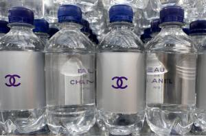 """Chanel mineral bottles are displayed on supermarket shelves at the Grand Palais transformed into a """"Chanel Shopping Center"""" during Paris Fashion Week"""