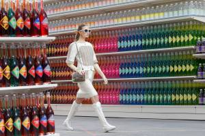 """A model presents a creation by German designer Karl Lagerfeld as part of his Fall/Winter 2014-2015 women's ready-to-wear collection for French fashion house Chanel at the Grand Palais transformed into a """"Chanel Shopping Center"""" during Paris Fashion Week"""